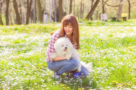 dia soleado: Feliz hermosa mujer joven, disfruta de la naturaleza con su perro, en el día soleado de primavera en el parque.