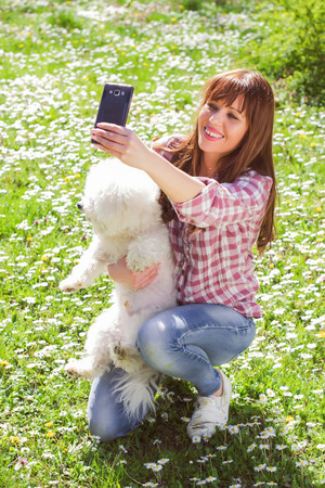 dog park: Happy beautiful young woman, enjoying nature with her dog, taking selfie with phone in the park. Stock Photo