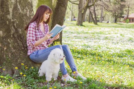 campo de flores: Hermosa mujer joven que lee un libro. El tiempo libre con su perro en el parque. Foto de archivo