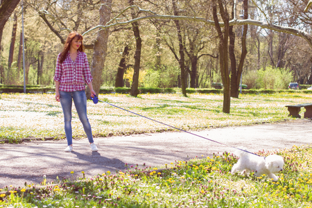 dog park: Happy beautiful young woman, enjoying nature with her dog, at sunny spring day in the park.