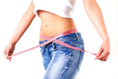 cintura: Mujer atractiva de la cintura delgada en pantalones vaqueros con cinta de medida espectáculo body.Diet delgada y control de peso. Foto de archivo