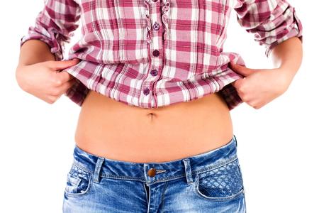 vientre femenino: cintura delgada de la hembra caucásica en los pantalones vaqueros y la camisa. Foto de archivo