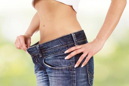 cintura: Mujer atractiva de la cintura delgada en pantalones vaqueros muestran delgado cuerpo. Foto de archivo