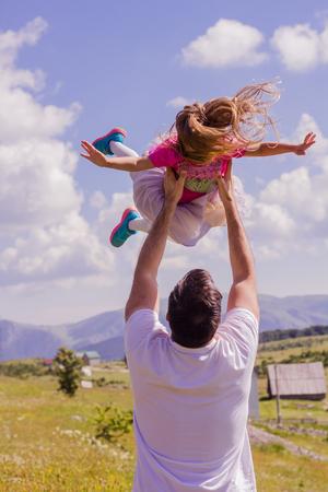 Vater mit Tochter spielen, wirft in der Luft Kind, Familie Spaß in der Natur auf.