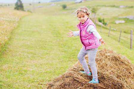 funny people: Little Girl playing on a haystack in a meadow, child outdoor activity.