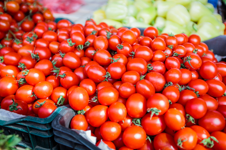 Fresh red ripe cherry tomatoes on the farmers market stand. Stock Photo