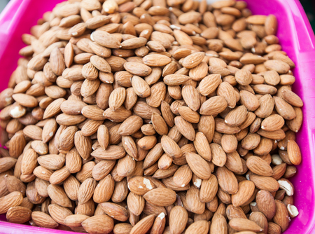 heap up: Heap of peeled almonds , close up, healthy fruit on open market. Stock Photo