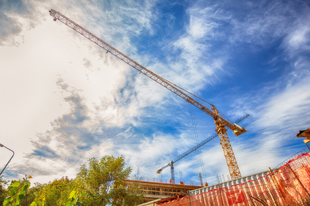 workforce: Construction crane on construction site over cloudy blue sky. Support and development business concept.