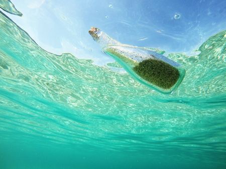 Message in a bottle floating in the sea. Glass bottle with sand and help message in the water.