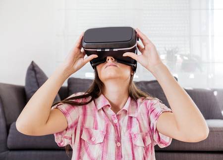 virtual reality simulator: Young woman using virtual reality glasses at home, female wearing VR headset.