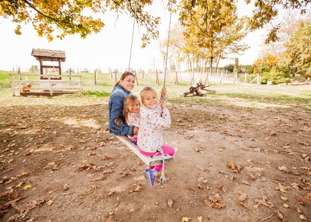 Smiling happy family relaxing nature swing outdoor autumn season.