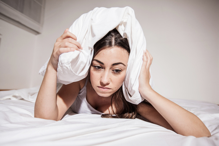 Female with insomnia cover her head with pillow in bed.