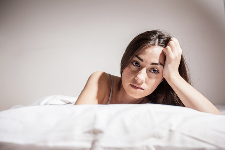 Depressed Young woman with insomnia in bed cant sleep.