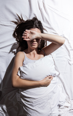 Young woman with insomnia cover her face with hand in bed. Imagens