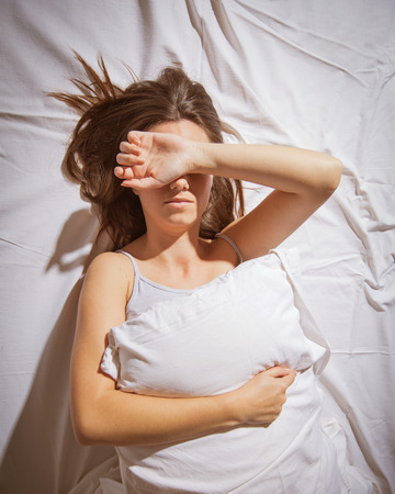 Young woman with insomnia cover her face with hand in bed. Stock Photo