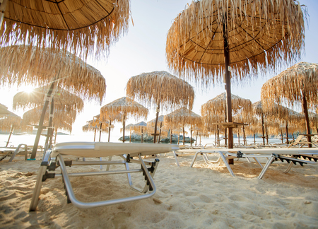 Sand beach with straw sunshades and sunbeds in morning, summer vacation