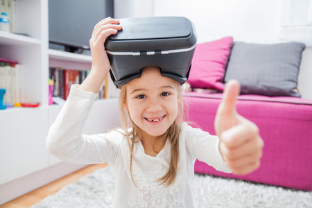 Child with Virtual Reality headset at home, children and technology