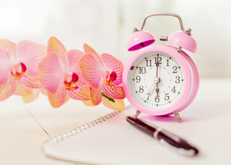 Retro alarm clock with flower orchid and diary book