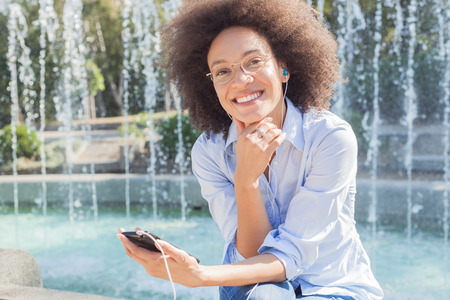 Beautiful Happy Young Mixed Race Woman With Earphones Using Phone, Casual Wear, Outdoor Portrait , Looking At Camera