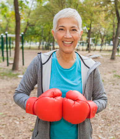 Portrait Of Fit Senior Woman With Boxing Glove At Outdoor Fitness Park In Sportswear. Active Old People Healthy Lifestyle Stock Photo