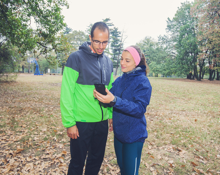 Fitness young woman show to sporty man on the smartphone, plan for exercising in forest. Sporty woman and men prepare for workout.