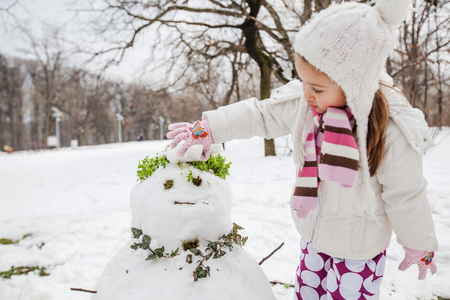 Child make a snowman in the park at winter day. 写真素材
