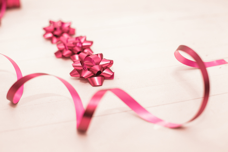 Set of decorative magenta bow over wooden background with space for text.