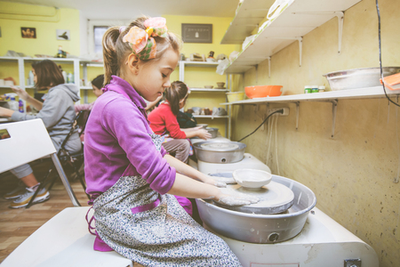 Young potter artist molding clay at pottery wheel at workshop.