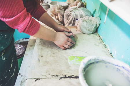 Female potter hands molding clay on table at pottery workshop.