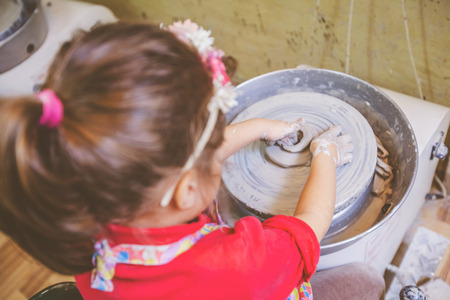 Top view of little girl making clay on pottery wheel at workshop.