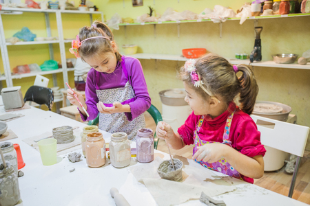 Two little young artist girl painting with brush clay vase at table in ceramic studio