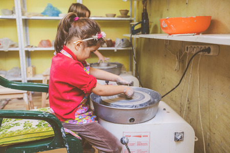 little girl learning shaping clay on pottery wheel at arts workshop Stock Photo