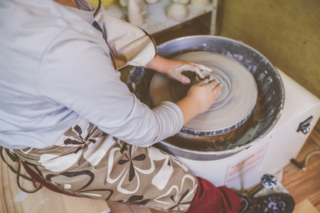 hands of young artist shaping clay on pottery wheel at workshop in ceramic studio Фото со стока