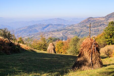 Rural autumn landscape. Traditional haystack in the fields. Beautiful countryside view in Serbia.