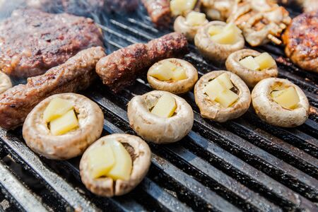 White mushrooms champignon filled with cheese preparing for barbecue Stock Photo