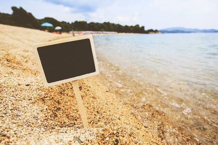 Summer vacation holiday concept. Empty wooden sign board for message on sand beach with seascape in background