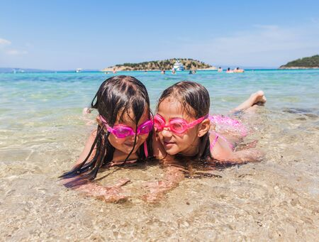 Happy children fun on the beach at summer holiday. Little girls wearing swimming goggles and lying in sea shallow water. Reklamní fotografie - 148277000