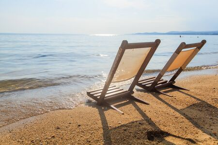Summer holiday and travel relaxing concept. Beach chair on the sand near the sea with clear blue sky in background.