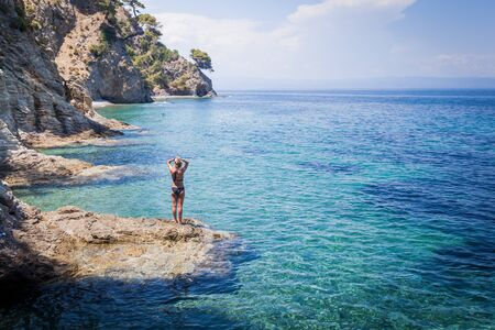 Summer holiday. Beautiful seascape of Greece. Rearview of attractive woman on the rock enjoy scenic turquoise sea view on vacation