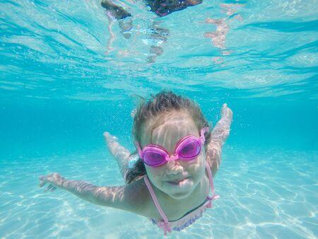 Fröhliches Kind Unterwasserporträt - Kleines Mädchen mit Schwimmbrille tauchen und schwimmen im Meerwasser - Sommerurlaubsspaß