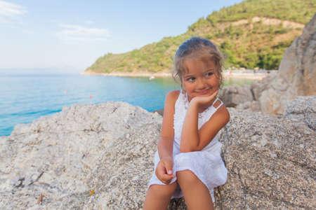 Portrait of cute happy little girl sitting on rocks shore. Beautiful summer seascape in background