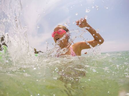 Happy child have fun splashing in sea water at summer holiday. Little girls wearing swimming goggles