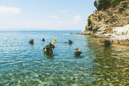 Group of scuba divers ready for diving in the beautiful Greece turquoise sea. Summer holiday activity.