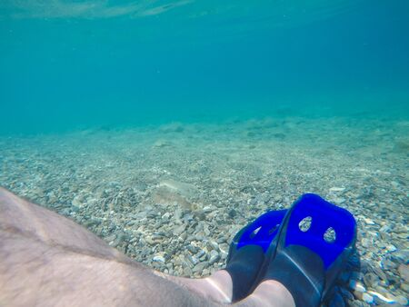Underwater photo of male legs with blue fins.