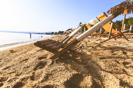 Summer holiday and vacation concept. Empty beach deck chair on sand near the sea at sunset. Imagens