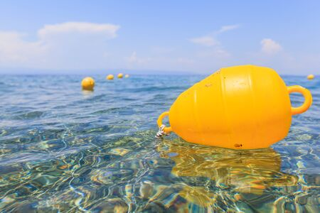 Yellow buoy floating on the sea. Clear water and blue sky in the background. Summer season. Imagens