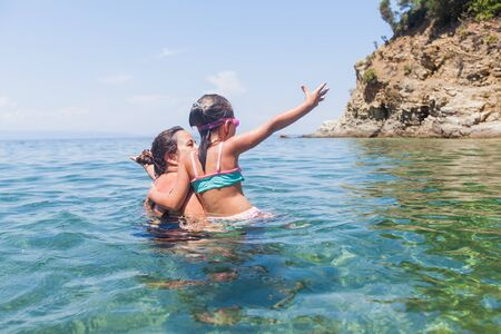 Happy family summer holiday - Mother and daughter having fun together in the sea during vacation