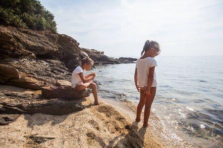 Two little girls explore rocks shore near the sea. Children at summer vacation  Reklamní fotografie