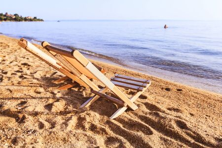 Summer holiday and travel concept. Empty  beach deck chair on sand near the sea at sunset. Imagens