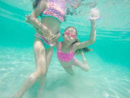 Funny children underwater portrait - Little girls wearing swimming goggles dive and swim in the seawater - Summer vacation fun